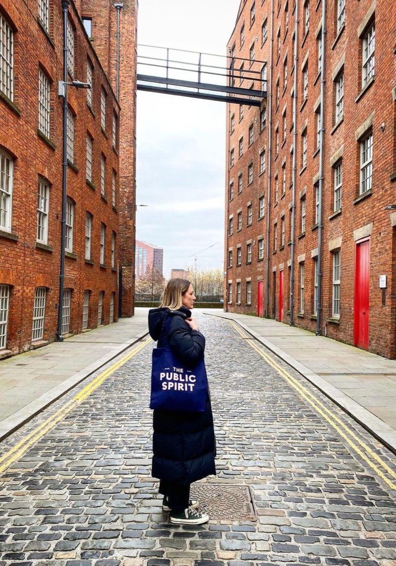 A woman stood on Bengal Street in Ancoats, in the centre of a cobbled road between two large brick warehouse buildings with a bridge overhead, woman is stood sideways wearing a The Public Spirit Tote Bag