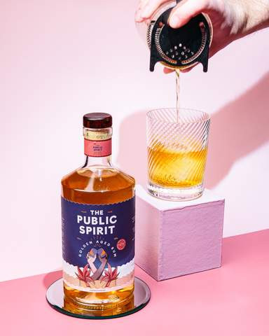 Photograph of a bottle of The Public Spirit Rum, and an engraved glass cocktail atop a pink cube with a hand pouring from a cocktail shaker into the glass
