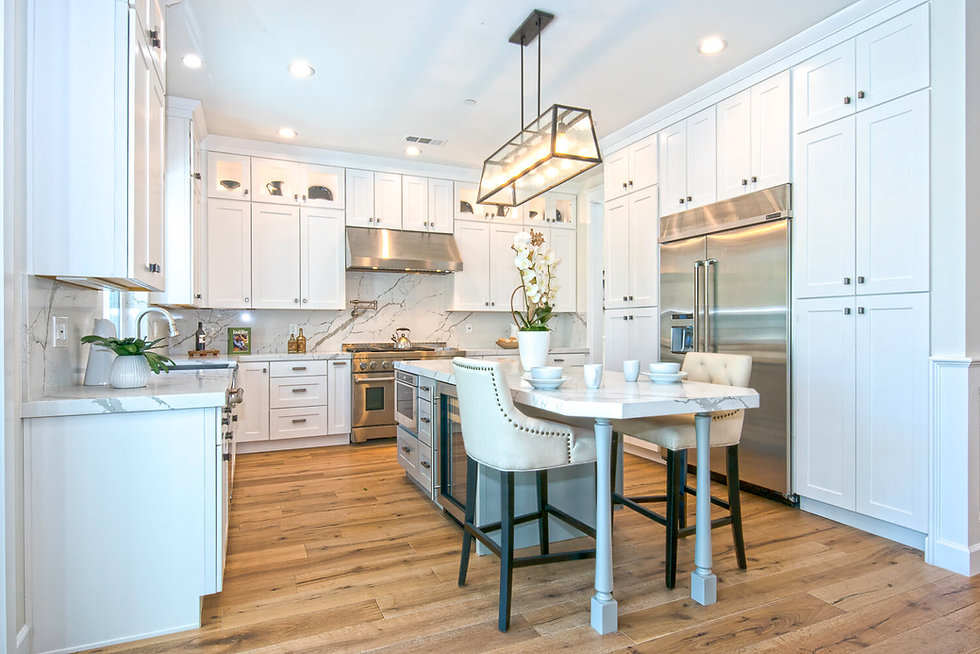 a los angeles kitchen remodel with white cabinets, luxury appliances and white marble countertops and backsplash