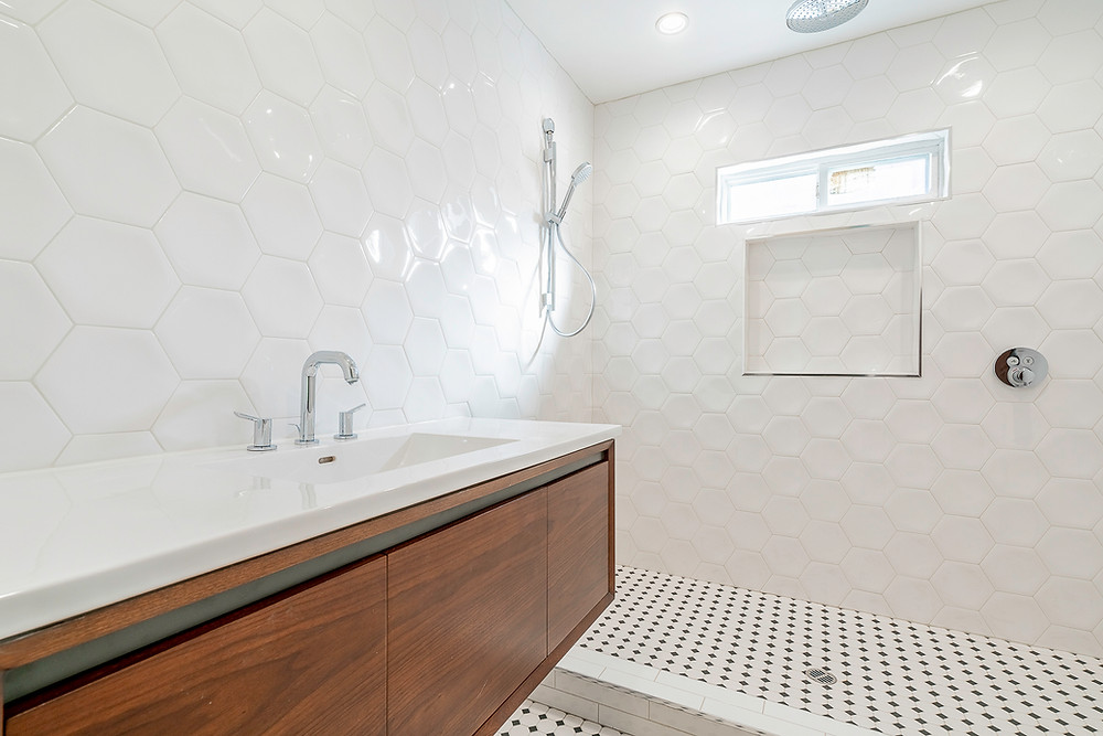 average bathroom with white floor to ceiling hexagon tile on the walls and black and white tile on the floors