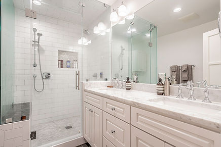 bathroom with a white double vanity and walk-in shower with subway tile