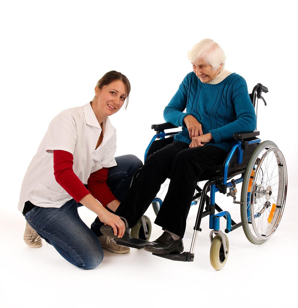 Eine Dame im Rollstuhl und eine Pflegekraft