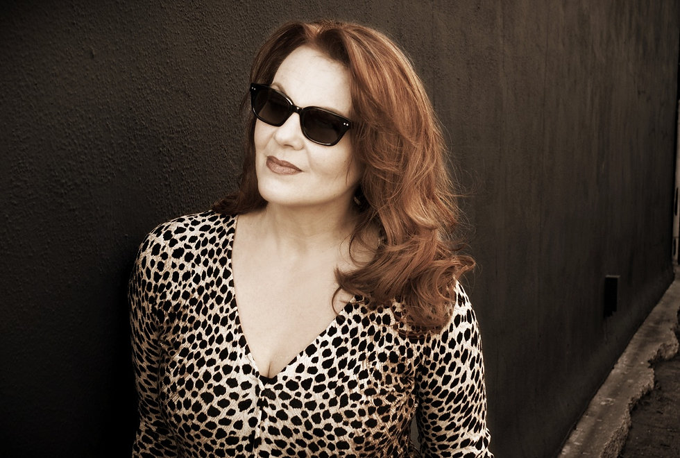 Woman with long red hair wearing sunglasses and a leopard-print sweater against dark wall.