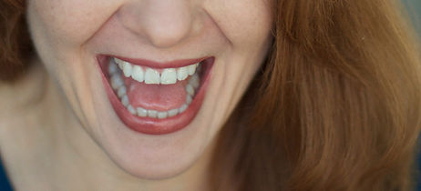 Woman with red hair laughing with eyes closed.