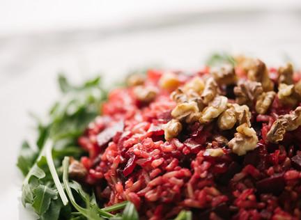 Riž s karamelizirano rdečo peso, rukolo in praženimi orehi