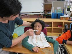 協助智慧班學生用餐拿湯匙的正確姿勢,幫助學生可以自行進食