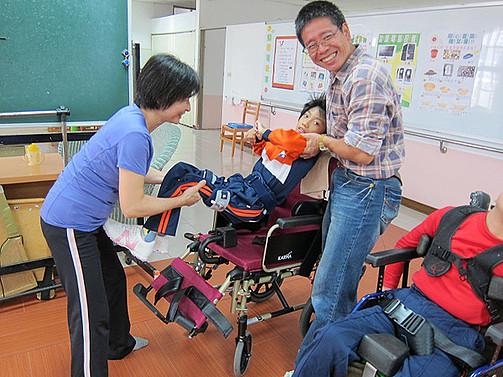 老師們合力將智慧班學生抬上輪椅