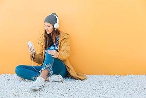 mujer-sentada-alfombra-usando-telefono-inteligente-escuchando-musica-auriculares_23-2148204623_edite