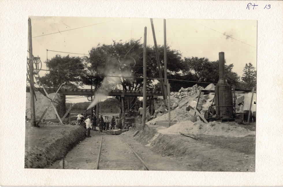 The trolley tracks being laid underneath the railroad.