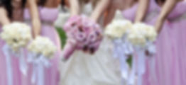 Photo of bridal party including bride in white wedding dress, and  four bridesmaids wearing light orchid strapless long chiffon dresses with rhinestone belts .Bridesmaids are carrying white rose flower bouquets adorned with light blue flowing ribbons.  The bride has an orchid rose bouquet embellished with rhinestone handle.
