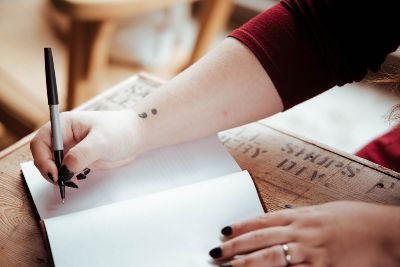 Person writing in notebook with semi colon tattoo