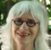 Fomatrice sophrologue à l'école de sophrologie du Nord-Est, esne à Reims, Caroline Rome, belle femme blonde souriante, avec frange et lunettes rondes sur fond de nature