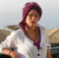 Fomatrice sophrologue à l'école de sophrologie du Nord-Est, esne à Reims, Valérie Lombard,  belle femme avec des bijoux colorés, cheveux bruns, courts, chemise blanche et foulard rose dans les cheveux, sur fond de mer