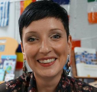 Fomatrice sophrologue à l'école de sophrologie du Nord-Est, esne à Reims, Elise El Rais, belle juene femme souriante, cheveux courts, boucles d'oreilles fantaisies avec chemise colorée