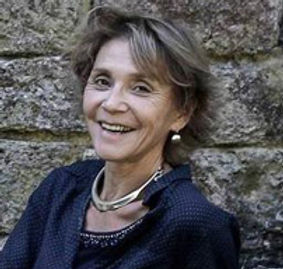 marie-claire bouthors, femme blonde, fondatrice de l'ecole de sophrologie du nord-est ESNE, souriante, bijourx en argent, chemise bleue, elle pause contre un mur en pierre