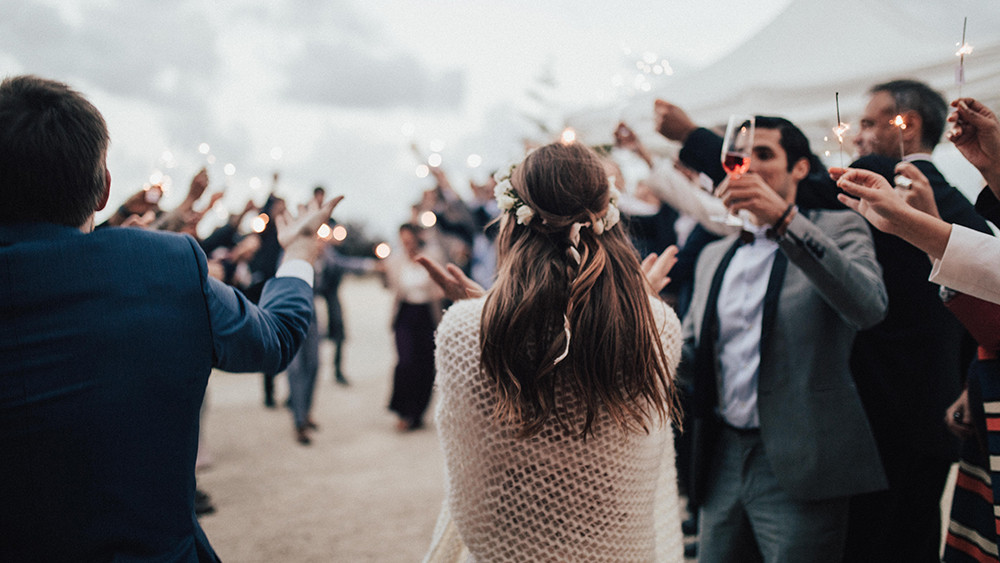Bride and groom greeted by guest with sparklers