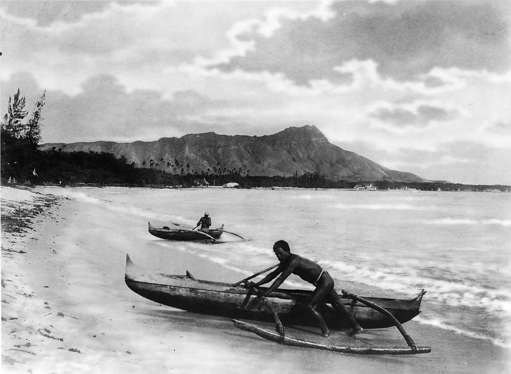 Dois nativos em uma canoa havaiana tradicional à beira-mar em Honolulu
