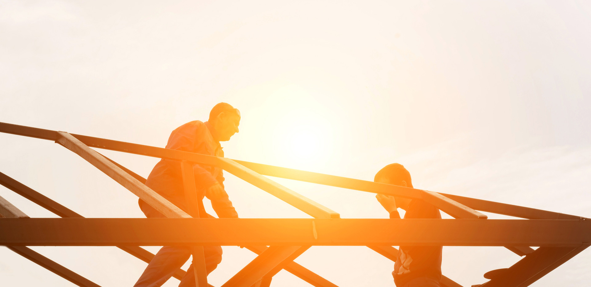 Group of builders at the top of the metal structure in the sunlight