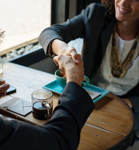 Woman smiling as she shakes hands with another man over coffee