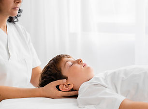 osteopathist-treating-kid-by-massaging-h
