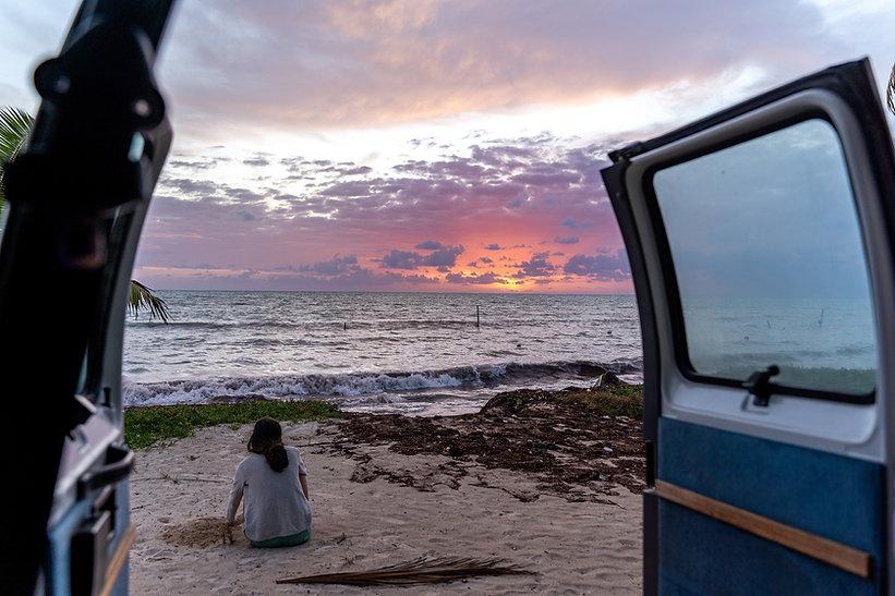 Women sat outside her mini camper van on