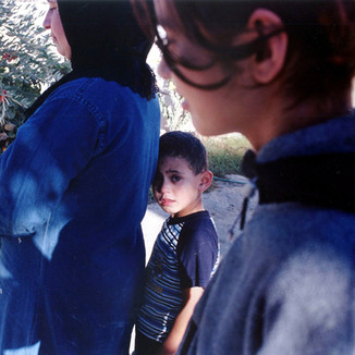 PALESTINE - Boy with his mother at the grave of his brother