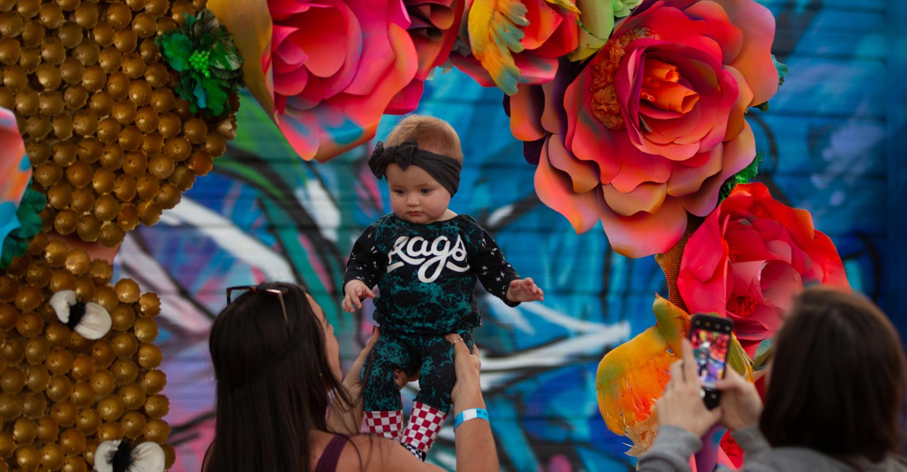 Baby underneath Billy Hensler mural