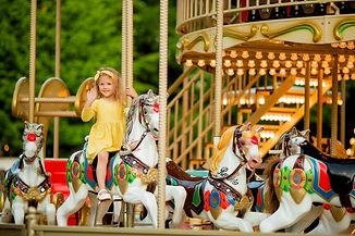 Adorable little girl near the carousel o