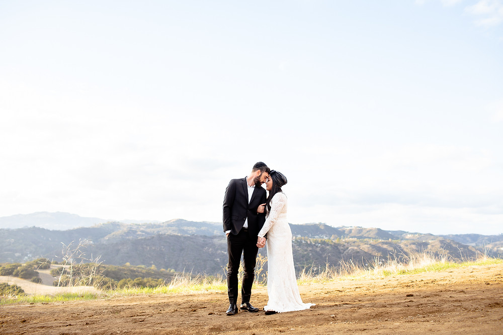 bride snuggles with groom on mountain top