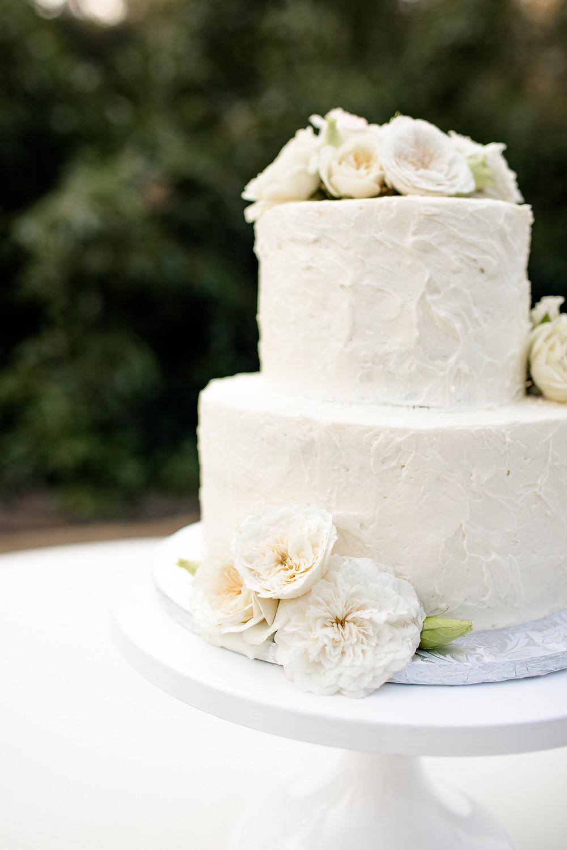 white wedding cake with white garden roses as decoration