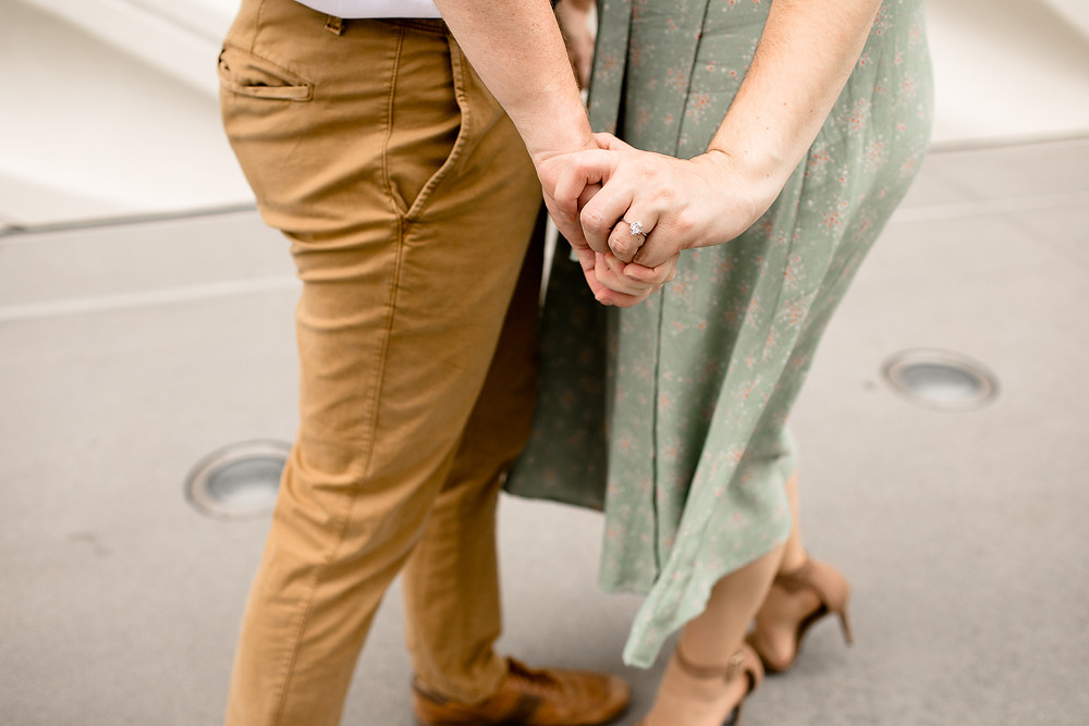 shot of couple holding hands with the focus on the engagement ring
