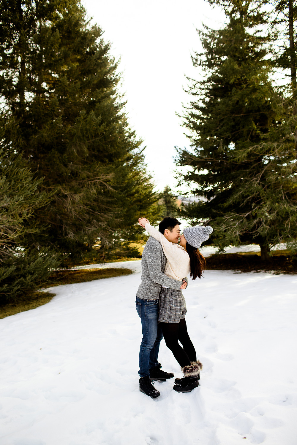 couple hugging and smiling in front of pine trees