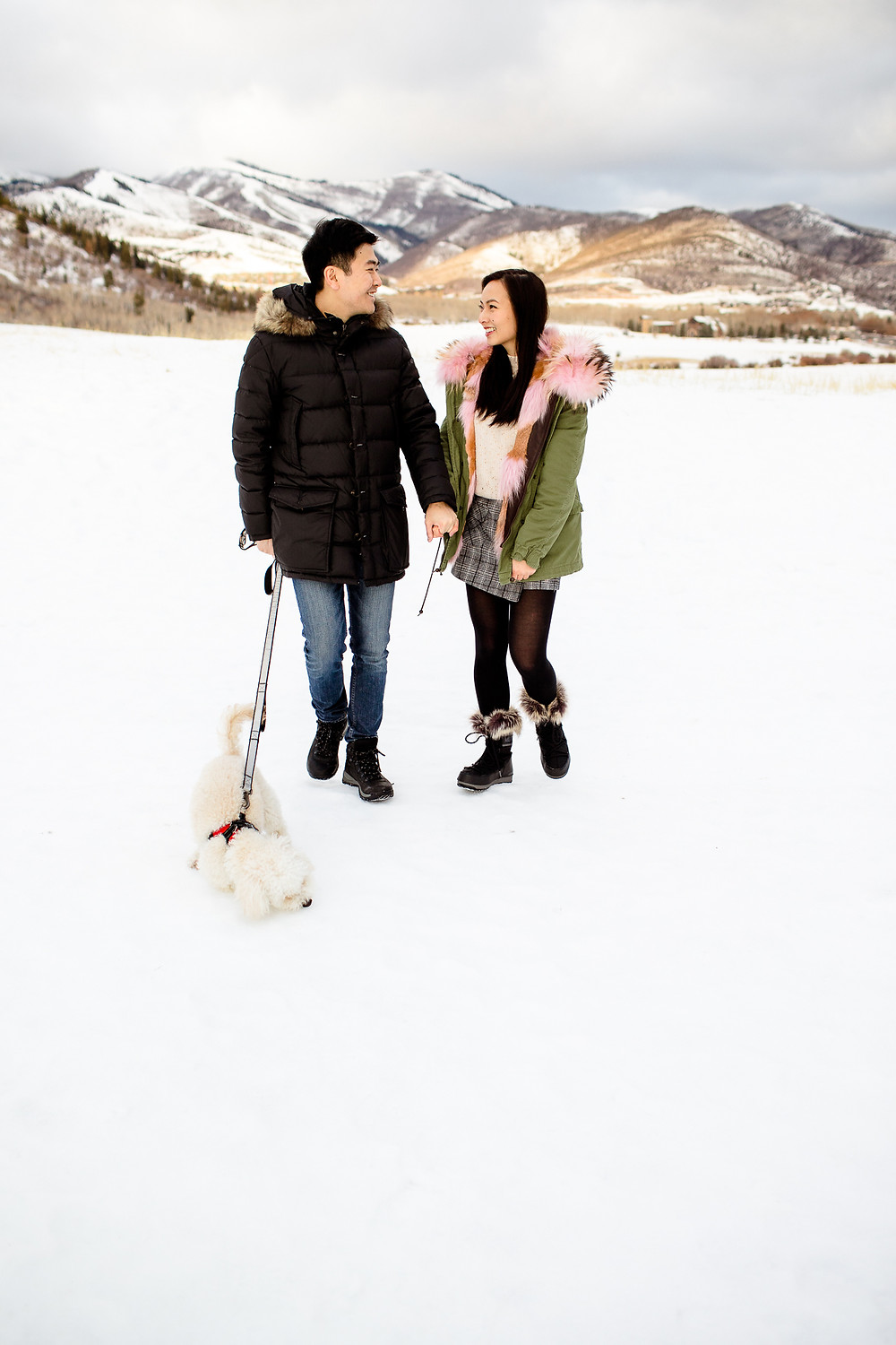 asian couple smile at each other while walking their dog outside of the big white barn in park city, utah