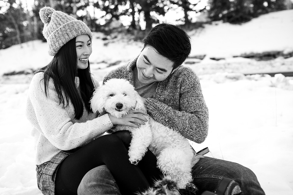 black and white photo of couple playing with their dog