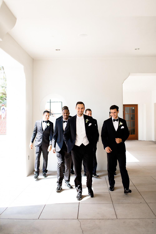 groomsmen in black tuxes smiling and walking