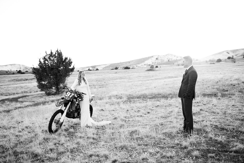 bride leaning against a dirtbike with her groom smiling at her