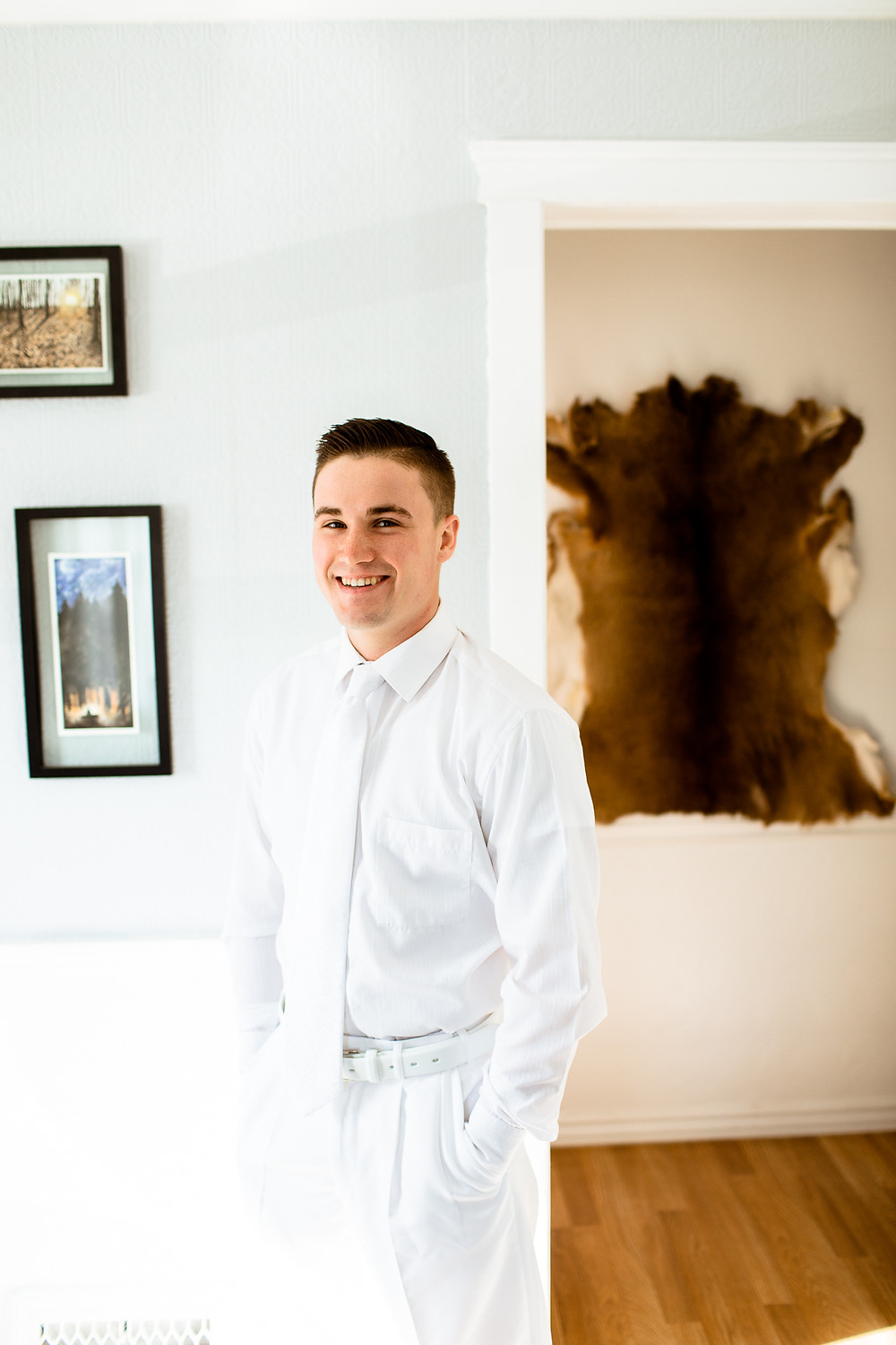 groom smiling at the camera in his living room