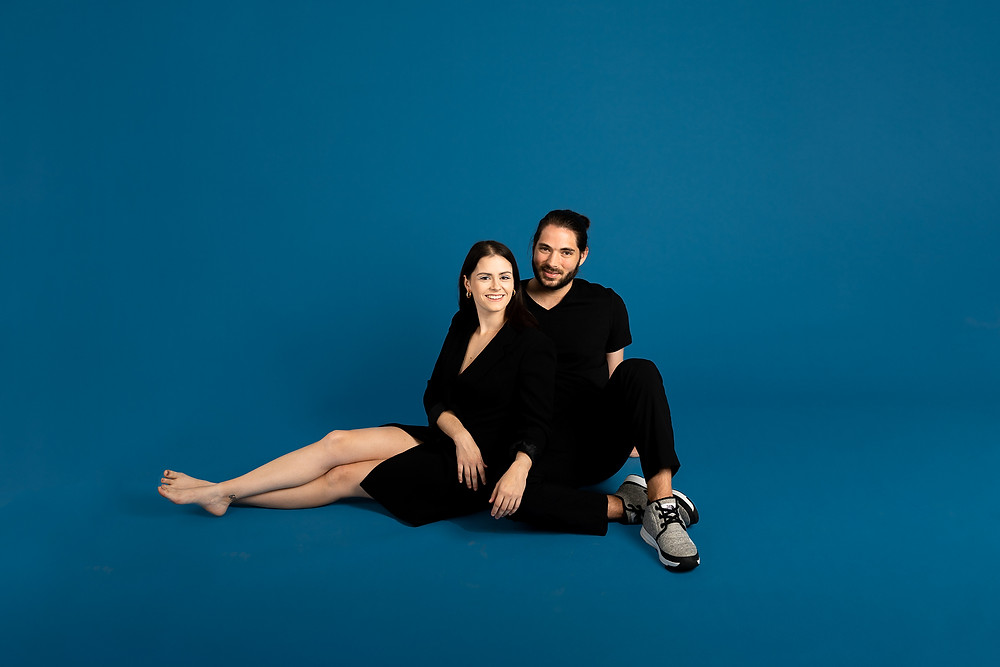 couple in all black sitting and smiling in a blue studio