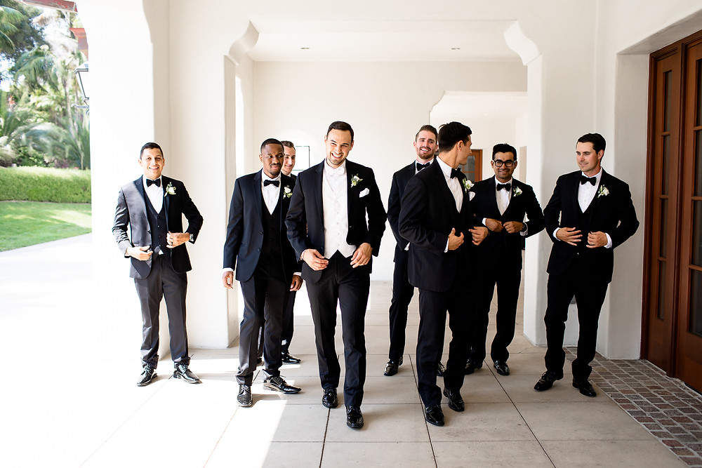groomsmen laughing and smiling in black tuxedos