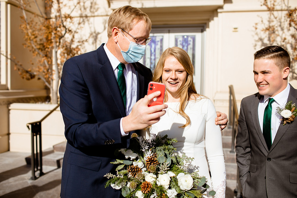 bride and groom smiling at a phone while facetiming