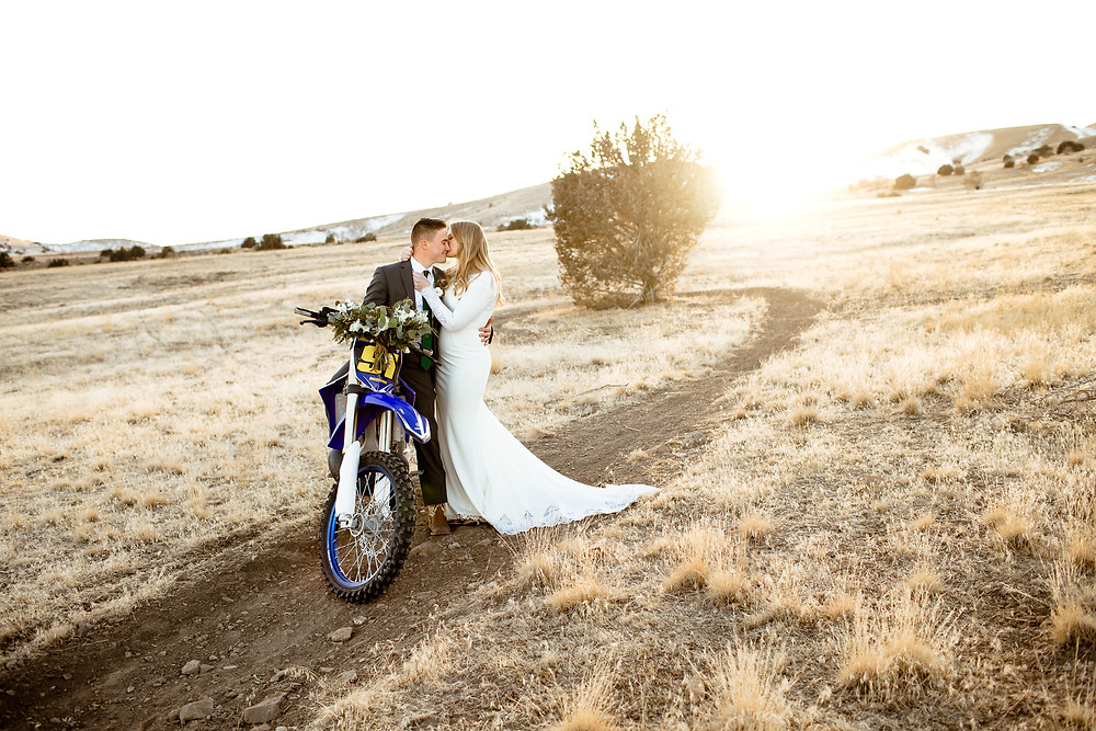 in payson, utah foothills bride kisses groom's face while he sits on a blue dirtbike
