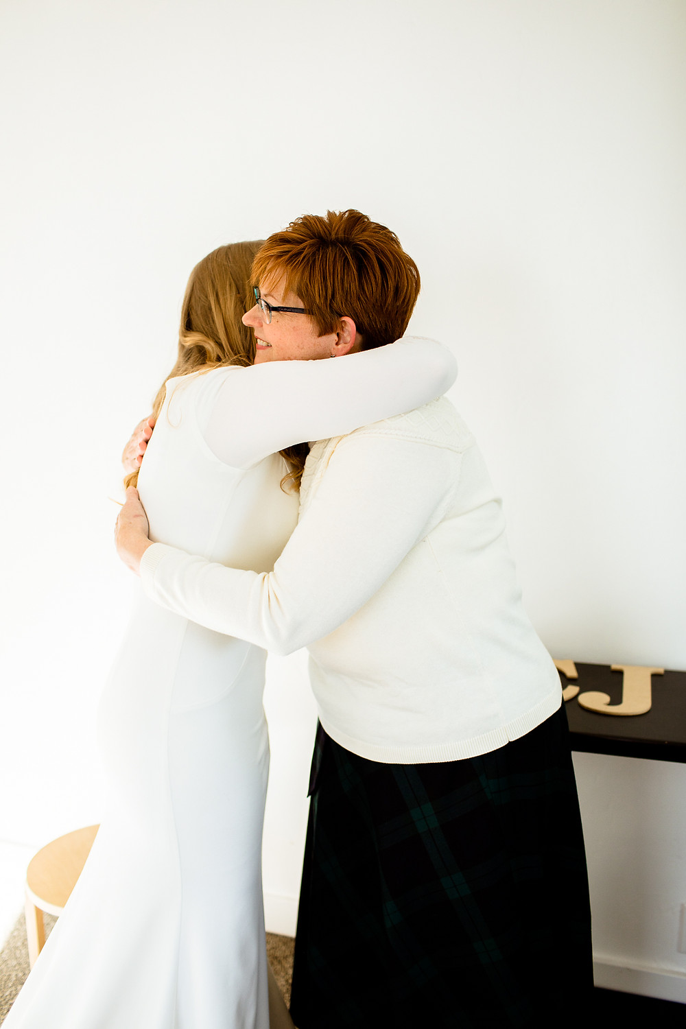 bride and her mom hugging on wedding day