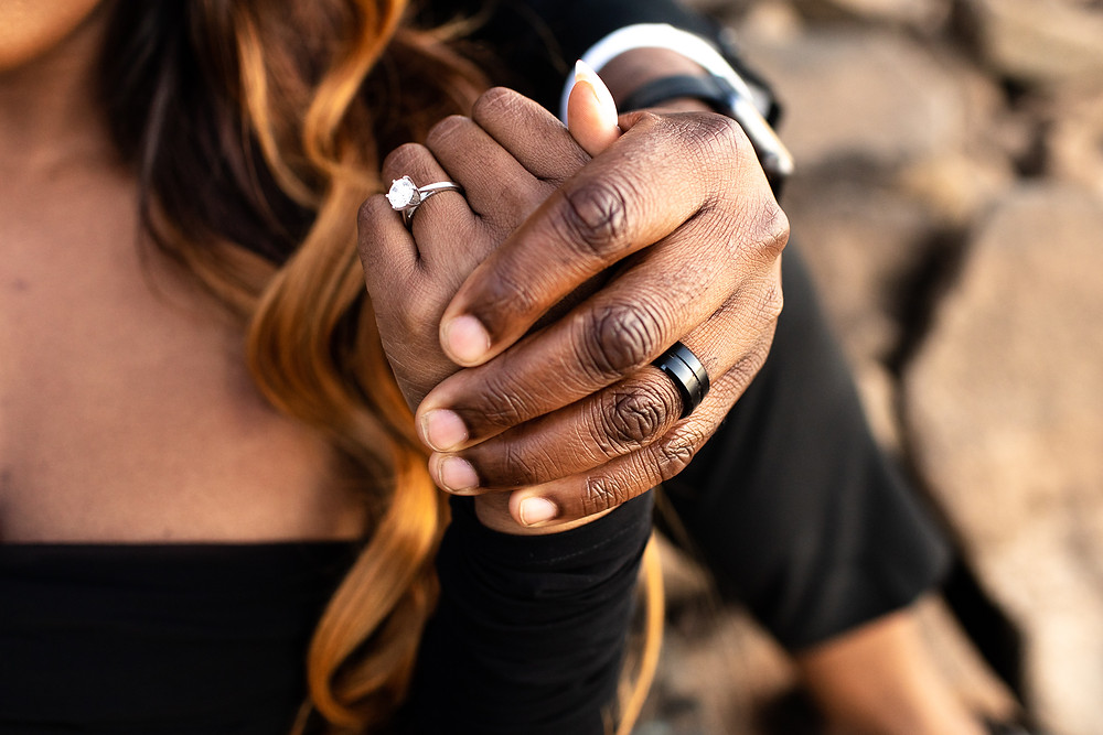 black couple holding hands with wedding ring and engagement ring showing