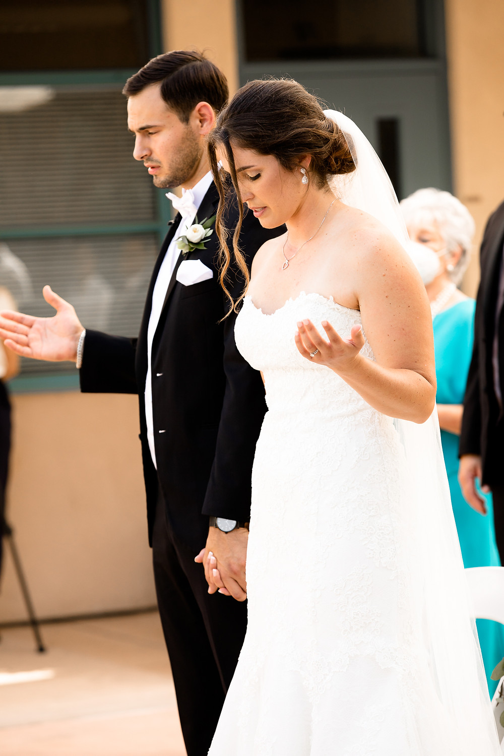 bride and groom lifting hands in prayer during catholic wedding ceremony