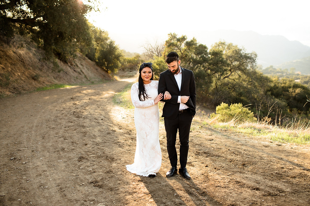 bride and groom walk arm in arm, smiling along california trail