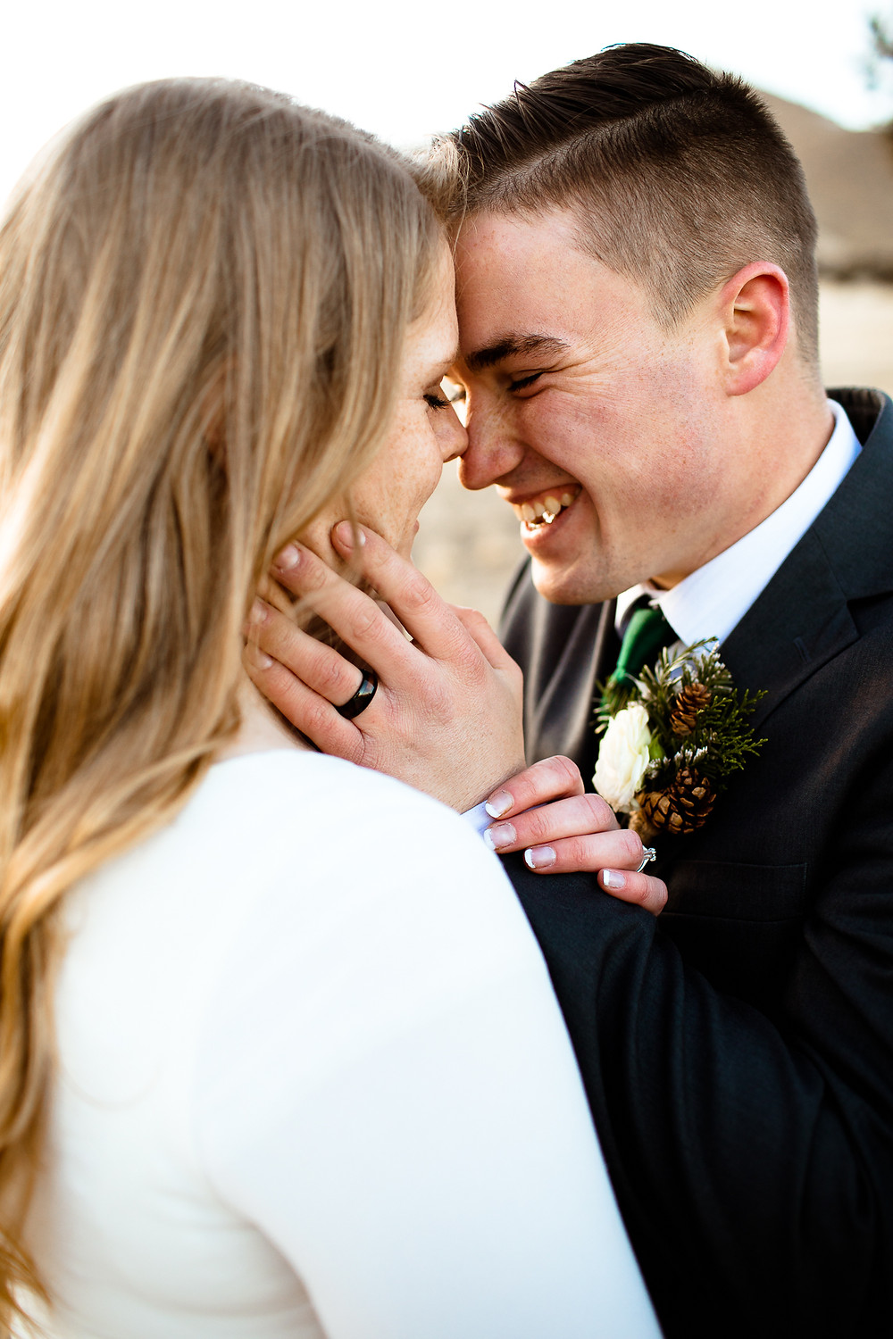 groom smiling while holding bride's face