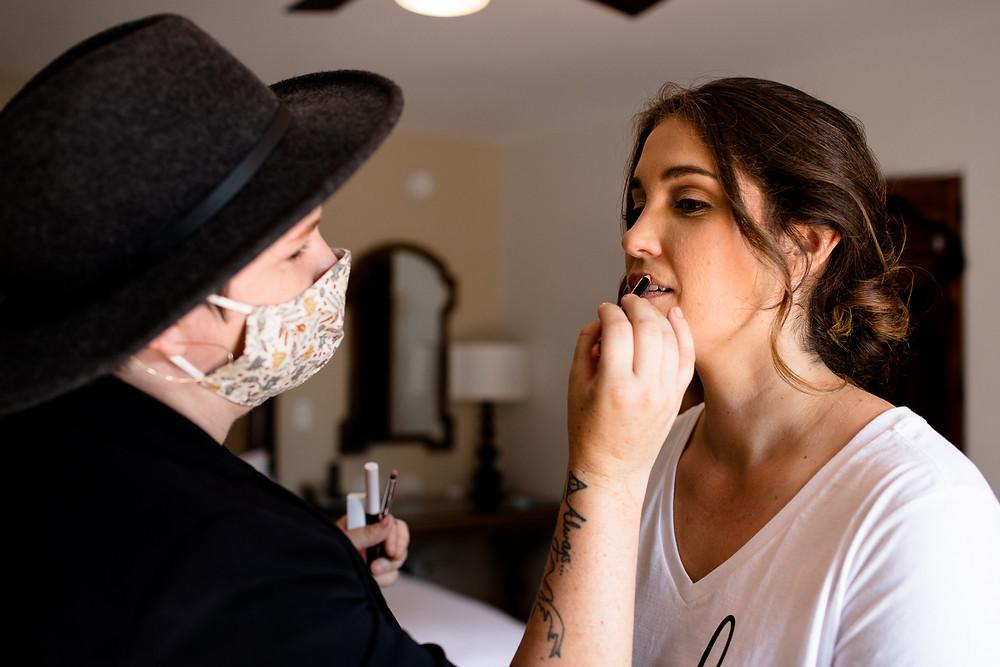 makeup artist puts final touches on bride's makeup