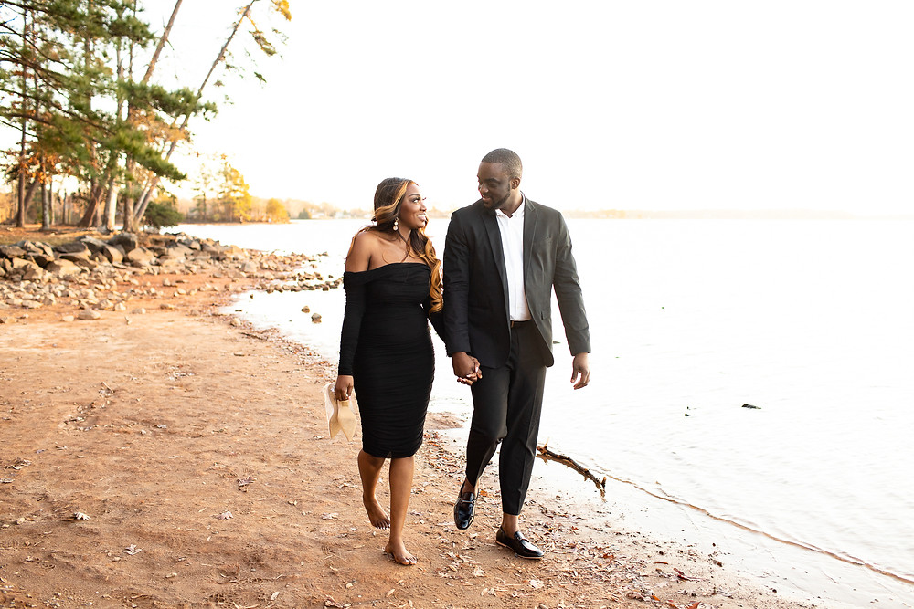 couple in all black walking along the water at jetton park