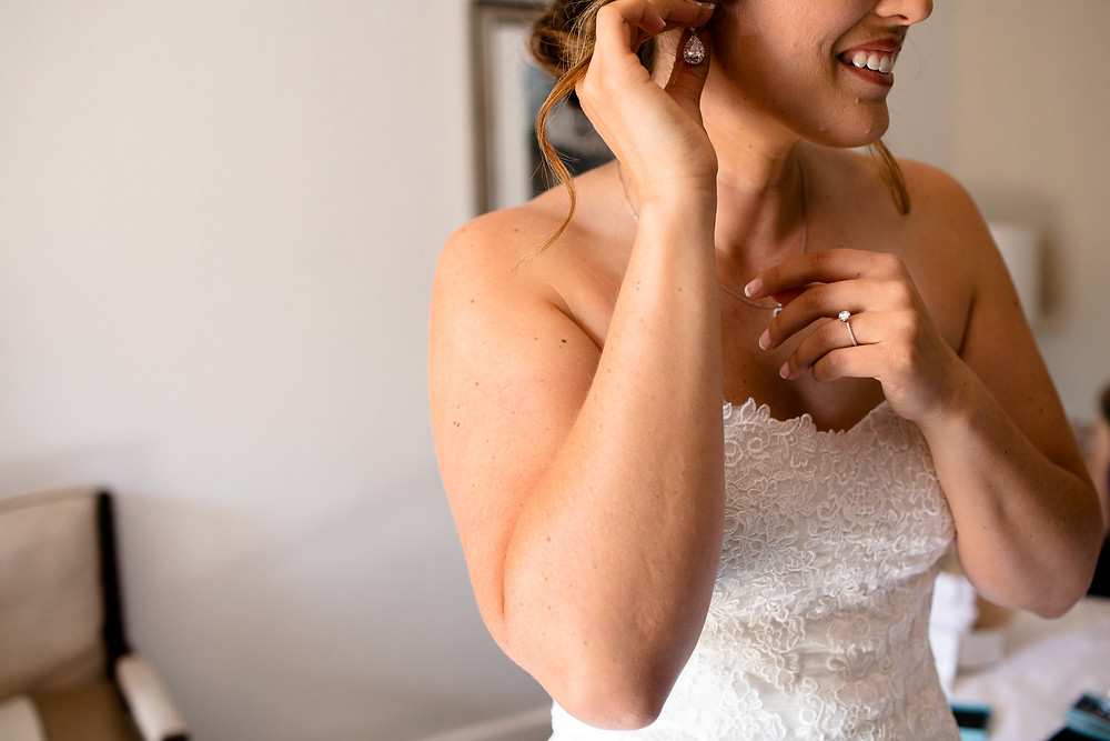 bride putting on earrings on her wedding day