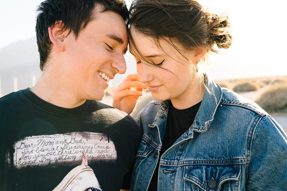 couple snuggling in a jean jacket and band tee shirt